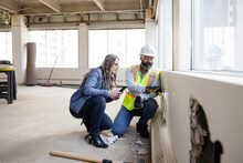 Architect And Construction Foreman Inspecting Wall In Empty Office