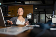 Businesswoman With Smart Phone Working At Laptop In Office