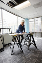 Architect Working On Plans In Empty Office Space