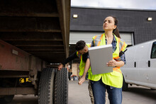 Female Warehouse Worker With Clipboard Inspecting Delivery Truck