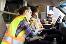 Warehouse Workers With Digital Tablet Talking In Van