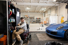 Disabled Male Worker In Wheelchair In Auto Body Shop