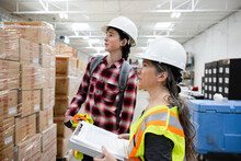 Manager With Clipboard Training New Employee In Warehouse