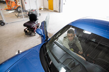 Disabled Male Worker Detailing Inside Of Sports Car In Auto Body Shop