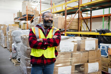 Portrait Confident Male Warehouse Worker In Reflective Vest