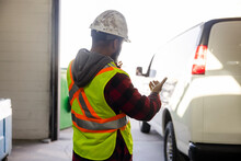 Warehouse Worker Guiding Delivery Van Into Loading Dock
