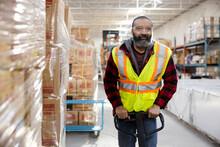 Male Warehouse Worker In Reflective Vest Using Pallet Jack