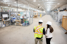 Warehouse Managers In Hard Hats Talking