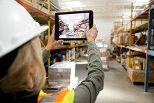 Female Warehouse Worker Photographing Shelves With Digital Tablet
