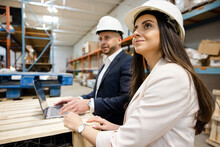 Business People In Hard Hats Working At Laptop In Warehouse