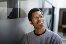 Thoughtful Young Businessman Wearing Eyeglasses In Office