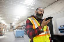 Male Warehouse Worker Talking On Speaker Phone