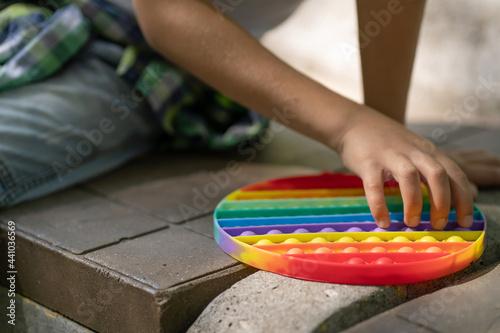 Obraz na plátně A child plays pop it on a park bench