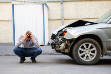 Young Man Driver In Car Accident Holding His Head Near Broken Car On The Road After Car Accident. Caucasian Man Facepalm Holding Head Injury After Accident
