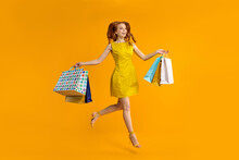 Full Length Image Of Charming Young Redhead Woman Wearing Yellow Dress Smiling, Caucasian Lady Is Carrying Colorful Paper Shopping Bags, Jumping And Looking Away Isolated Over Yellow Studio Background