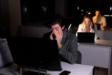 Young Caucasian Tired Brunnete Man In Suit Sits At Night In Office, Eyes Hurt From Overexertion, Suffering From Headache. Male Office Worker Does Not Meet The Deadline. Copy Space