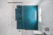 Decorated With Dark Aquamarine And White Colors. Modern Tiled Bathroom With Shower Zone, New Sink And Toilet.
