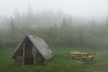 Abandoned Wooden Cabin In A Misty Forest. Summer Foggy Mysterious Landscape
