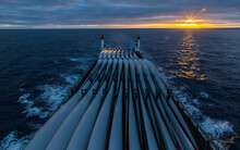 Transportation Of Blades For Wind Turbines On A Cargo Ship Across The Ocean At Sunset.