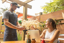 Barista Offering Coffee Cup To Freelancer Smiling Working On Laptop With Coffee Cup In An Artisanal Coffee Shop. Plumes And Plants Being Seen Through Wood Planks Wall Gaps In The Background.