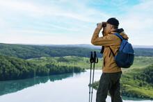 Hiker Man Looking In Binoculars On The Mountain. Hiking Active People Lifestyle.