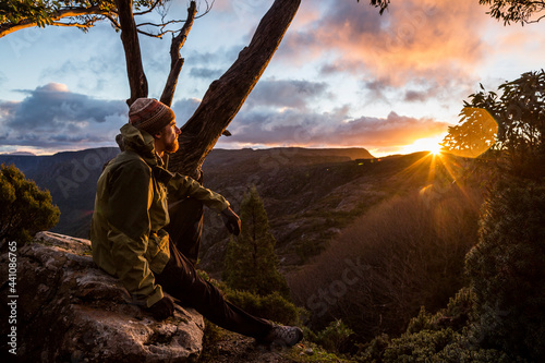 A hiker watching the sunset beside the Overland Track