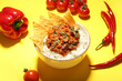 Leinwandbild Motiv Bowl with tasty chili con carne, rice, nachos and vegetables on color background, closeup