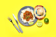 Leinwandbild Motiv Plate with tasty chili con carne, rice, lime and sombrero hat on color background