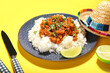Leinwandbild Motiv Plate with tasty chili con carne, rice, lime and sombrero hat on color background, closeup