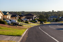 Cars Parked In Driveways Of Houses Beside Suburban Road