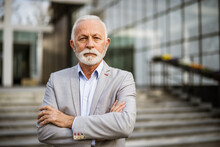 Outdoor Portrait Of Serious Senior Businessman In Front Of Company Building.