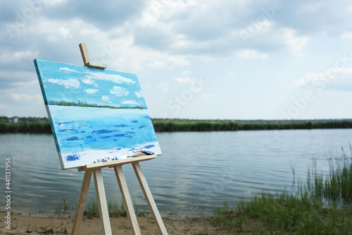 Wallpaper Mural Wooden easel with unfinished painting near lake