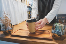 Close Up Image Of A Barista Serving Coffee In A Cozy Cafe With A Tip Box Nearby