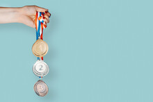 Woman's Hand Holding Three Medals (gold,silver,bronze).concept Of Award And Victory.copy Space
