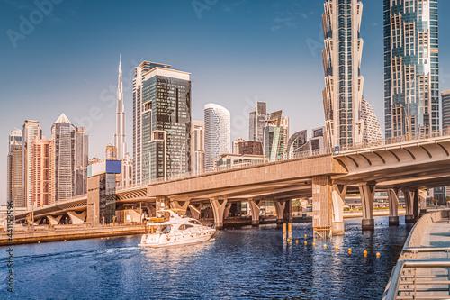 Fotografia Luxury speedboat sails under the bridge in Dubai Downtown Center with stunning v