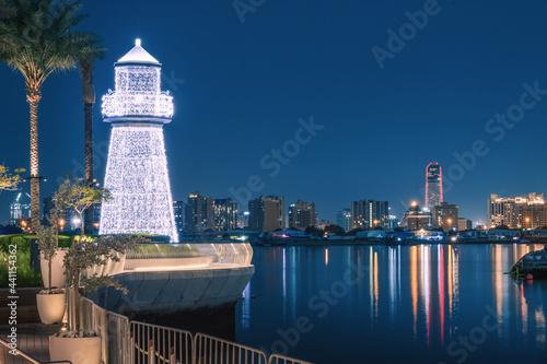 Photo Illuminated decorative lighthouse near the parking lot of yachts and ships in the Dubai Creek Marina Harbor