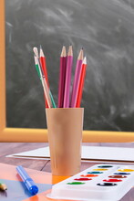 Close-up Of Multi Colored Pencils With Water Color Paints On Table