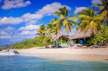 Straw Bungalows Of Hippie Camps On The Coast Of The Dominican Republic On The White Sandy Beach Of Atlantic Ocean On The Island With Coconut Palms Above The Sea Waves
