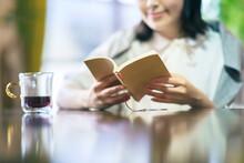 暖かい雰囲気の空間で、本を読む若い女性
