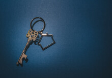 Vintage Key And House Shape Keychain On Blue Background.properties Investment Concept.