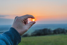 Hand Holding The Sun During Sunset