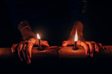 Close-up Of Hands Burning Candles