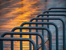 Wet Bicycle Rack In City During Sunset