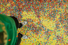 Low Section Of Person Standing On Multi Colored Confetti