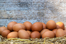 Group Of Eggs On Straw With Wooden Background