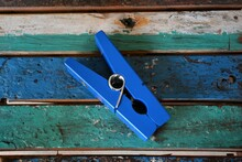 Close-up High Angle View Of Wooden Blue Oversized Clothespin On Blue And Teal Wood Boards
