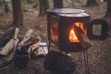 Winter Camping. Chopping Wood With An Axe And Stoking The Wood Stove.
