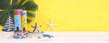 Nautical Concept With Sea Life Style Objects As Boat, Driftwood Beach Houses, Seashells And Starfish Over Wooden Table And Yellow Background