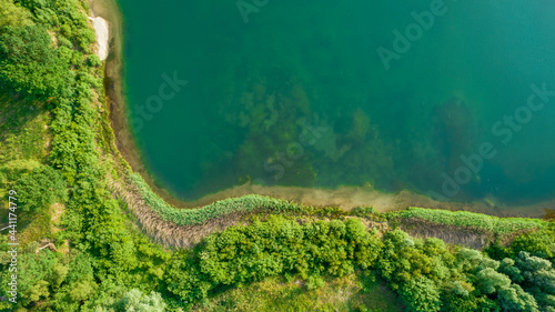Valokuva Aerial view of a picturesque place where transparent turquoise water of a forest lake meets a stony shore with trees in spring