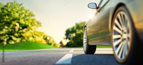 Fotografie, Obraz Car on sunny road with green landscape